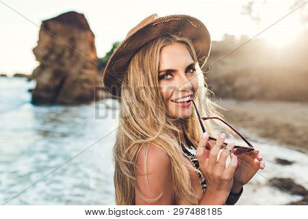 Closeup Portrait Of Attractive Blonde Girl With Long Hair Posing On Rocky Beach. She Wears Bikini, H