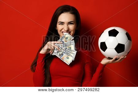 Beautiful Brunette Woman In Tight Red Dress Hold Soccer Ball In One Hand And Bites A Wad Of Dollars