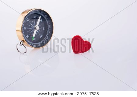 Compass Near A Red Heart On A White Background