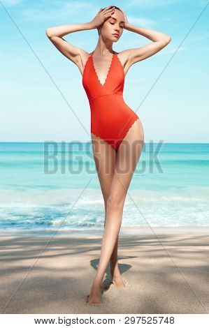 854372f389 Beautiful sexy lady on tropical beach. Fashionable woman with slim perfect  figure walking in front