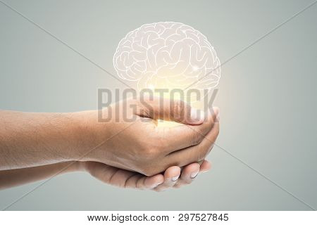Man Holding Brain Illustration Against Gray Wall Background. Concept With Mental Health Protection A