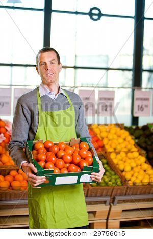 A friendly grocery store owner with a box of ripe tomatoes
