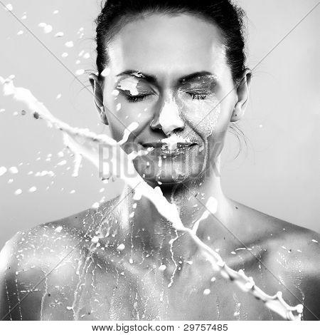Photo of beautiful woman in sprays milk