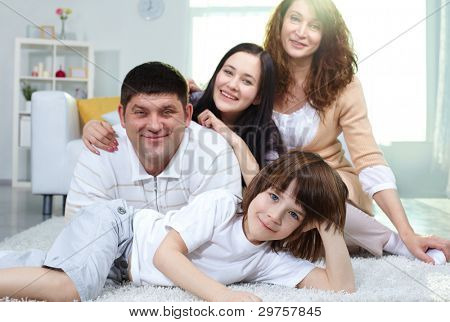 Family of four looking at camera while spending time together at home