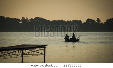 Couple Of Anglers Flowing By Small Boat On The Lake At Morning.
