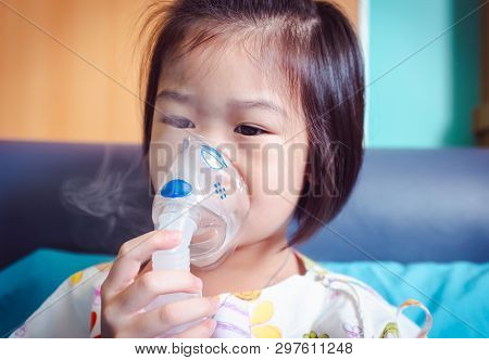 Sad Asian Child Holds A Mask Vapor Inhaler For Treatment Of Asthma. Breathing Through A Steam Nebuli
