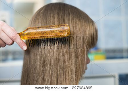 Mother Hand With Brush Combing Long Fair Hair Of Cute Child Girl After Bath On Blurred Interior Back