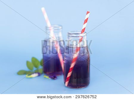Butterfly Pea Juce In Grass Bottle With Leaf And Flower On Light Blue Background, Herb Dink For Heal