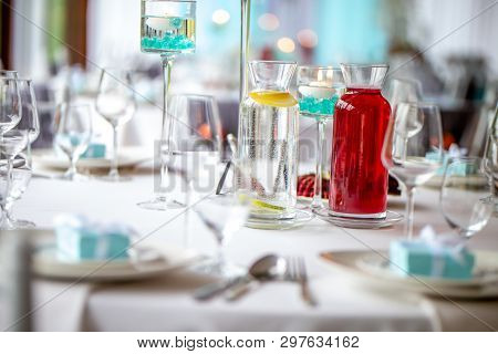 Jugs With Lemonade On Table With Food At Wedding Party Or Banquet. Water With Fresh Lemon And Red Li