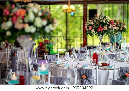 Wedding Table Decoration. Beautiful Bouquet Of Flowers In Vase On The Table, Next To Plates,  Glasse