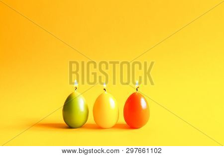 Traditional Easter decor. Group of bright burning paraffin candles in the shape of colorful eggs on soft warm yellow background. poster