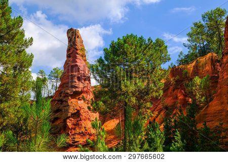 Roussillon Ochre Deposit: Beautiful Big Red Ocher Peak, Blue Sky And Green Pines.