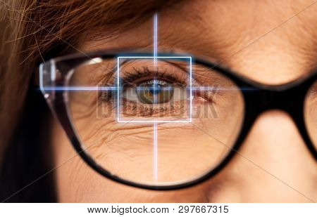 vision, eye surgery and ophthalmology concept - close up of face of senior woman in glasses with laser light