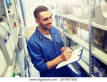 car service, repair, maintenance and people concept - smiling auto mechanic man or smith writing to clipboard at workshop or warehouse poster