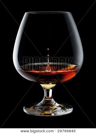 Copa de brandy con gotas y salpicaduras sobre fondo negro