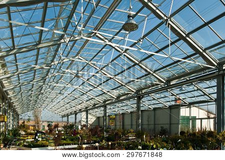 A Garden Centre With A Glass Roof Under A Blue Sky