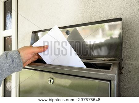 A Man Hand Putting Mail In Mailbox