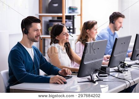 Happy Young Customer Service Executives Using Earphones Working In Call Center