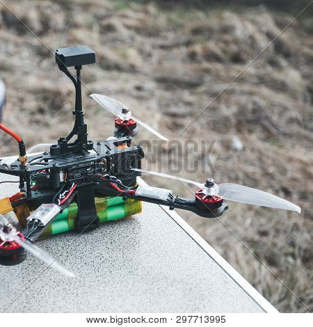 Fpv Drone Lies On The Table Near The Laptop And Control Panel. The Pilot Sets Up His Racing Drone Be