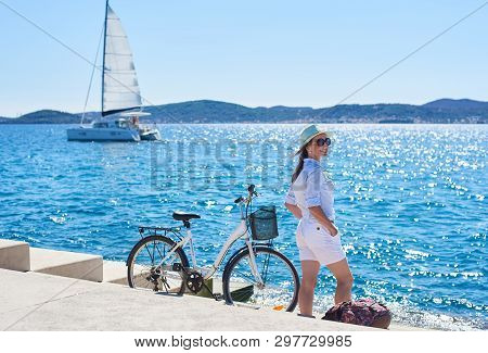 Pretty Smiling Tourist Girl In White Clothing And Sunglasses Standing At Bicycle And Backpack On Pav