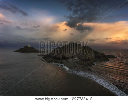 Soft Clouds At Dusk Over Mumbles Lighthouse In Swansea, South Wales, Uk