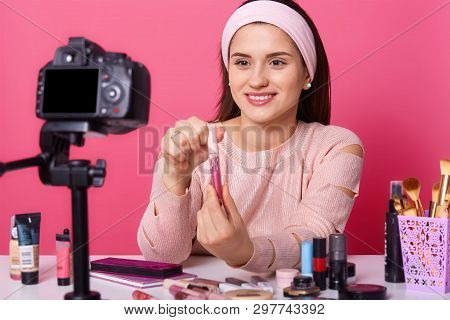 Image Of Adorable Young Woman Tests Some Beauty Products And Shows Lip Gloss To Her Followers In Blo