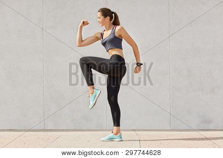 Young Sporty Woman Doing Exercise Against Gray Background, Dressed Top, Leggins, Sneakers, Has Pony