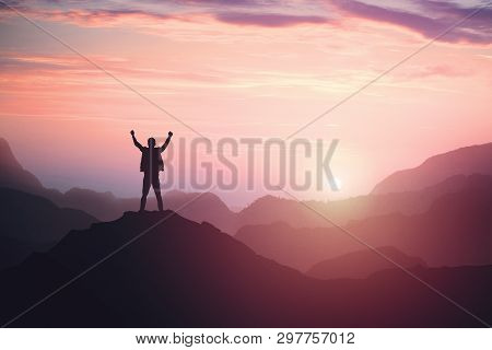 Victorious Male Person Standing On Mountain Top With Arms Raised. Winning And Success