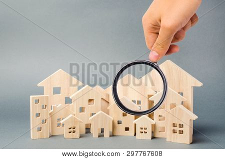 Wooden Houses And Magnifying Glass. Property Valuation. Home Appraisal. Choice Of Location For The C
