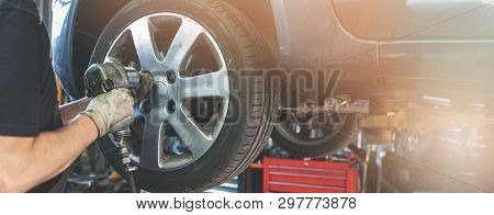 Car Mechanic Screwing The Wheel At Auto Repair Garage