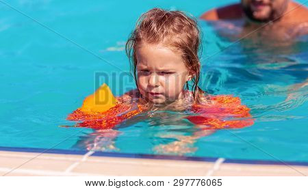 happy child girl learning swimming with inflatable armbands poster