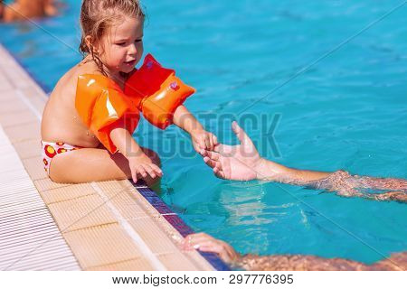 Little Girl Learning To Swim In Swimming Pool.