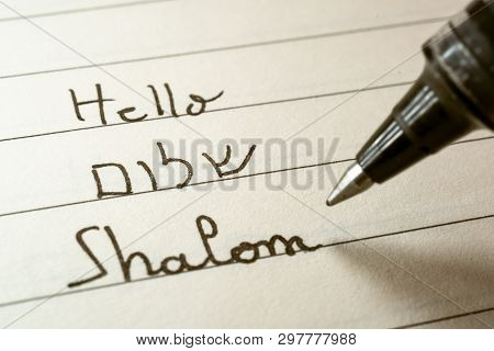 Beginner Hebrew Language Learner Writing Hello Shalom Word In Hebrew Alphabet On A Notebook Close-up