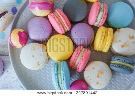Close Up Multicolored French Macaron Cakes On Blue Plate And White Wooden Background. White, Yellow,