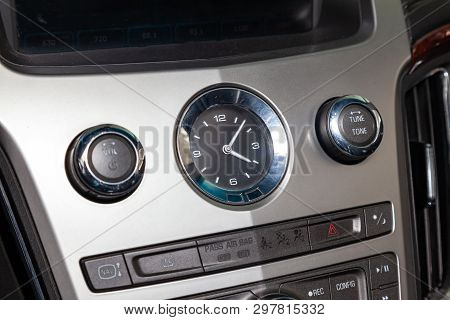 The Watch On The Dashboard Of Car Is Close-up, Covered With Natural Black Leather And Brown Woooden