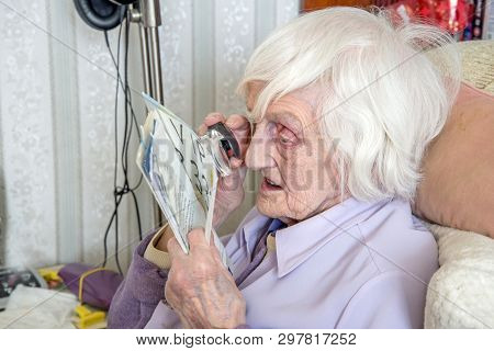 Visually Impaired Elderly Woman Reading With Magnifying Loupe.