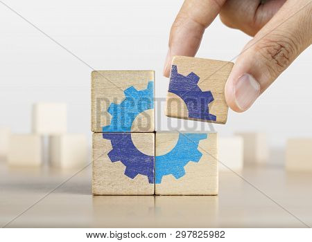 Hand Putting The Last Piece Of Wooden Blocks With The Gear Icon. Team Work, Unity, Partnership Or In