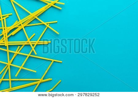 Flat Lay Photo Of Many Yellow Bendy Cocktail Straws. Top View Of Cocktail Straws On Turquoise Blue B