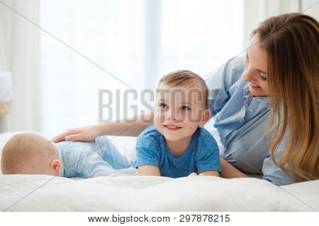 Happy middle aged mother with her children in a bed