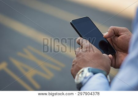 Closeup of businessman using smartphone on street to call a taxi cab. Detail of  black hand holding mobile phone while using high speed internet connection. Closeup of empty screen of cellphone.