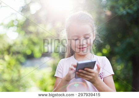 Child Is Using Mobile Phone. Kid Is Smiling And Looking At Screen Of Devices. Little Girl Is Playing
