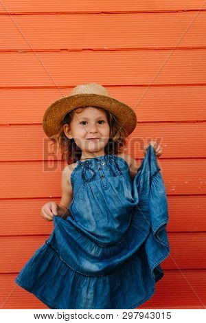 0a94a55024 Happy Child Girl In Summer Hat And A Beautiful Blue Dress Against Orange  Wall. Lifting