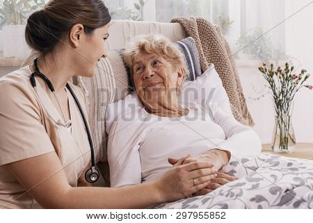 Positive Senior Woman Lying In Bed, Helpful Doctor In Beige Uniform Supporting Her