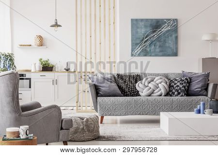Open Plan Studio Apartment With Small White Kitchen And Living Room With Grey Couch And Wooden Coffe