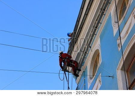 Construction Worker With Safety Harness Belt And Helmet, Working On Facade Renovation Of Historical