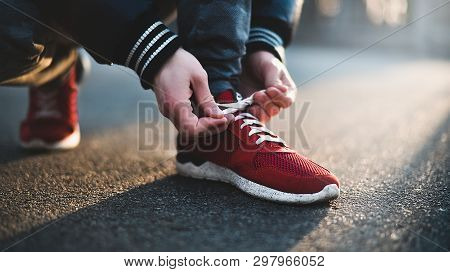 Hands Of Sportsman With Pedometer Tying Shoelaces On Sporty Sneaker. Running Equipment Concept. Shoe