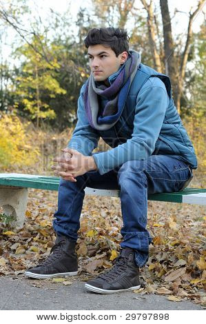 Young stylish man sitting in autumn park. Outdoor.
