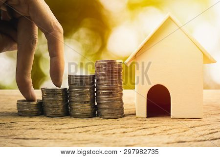 Real Estate Investment, Home Loan, Savings To Buy Home Concepts. House Wooden Model , Fingers Climb