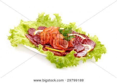 Tasty sausages, meat and greens on a plate
