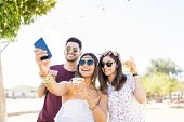 Cheerful young pals capturing memories with mobile phone at summer party poster